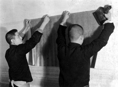 """为了使裱过的书画更加牢固、平挺,还要在背后覆两层宣纸,这道工序是""""覆背"""",也称""""覆活""""或""""裱背""""。加裱的覆背纸,必须选用棉料纸,薄厚也要与画心相配,才能使画心与覆背合二为一、天衣无缝。图为装裱师把覆过背的作品贴在墙上,用棕刷来回排刷,使其熨帖而平展。"""