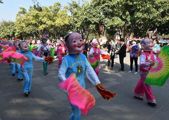 3月5日,人们在祭祖节上观看民间艺人街头表演。