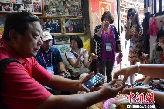 图为海外华文媒体代表品尝特色小吃、茶水。 张金川 摄