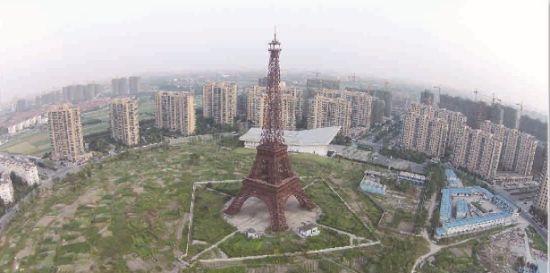 """于2001年就拿到7000亩地的广厦杭州天都城,目前开发体量仅仅只有总规划的一半左右。图为高108米、3:1比例建造的山寨版""""埃菲尔铁塔""""至今依然屹立菜地中央。"""