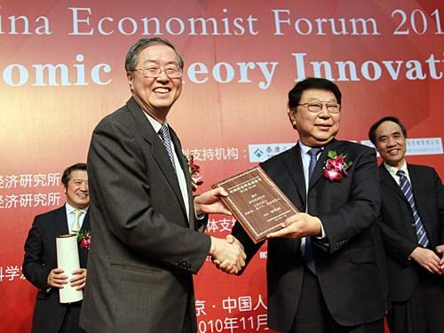 """""""中国经济学家年度论坛暨中国经济理论创新奖(2010)颁奖典礼""""于2010年11月20日在中国人民大学举行。上图为郑万通为周小川颁发奖牌。(图片来源:新浪财经 梁斌 摄)"""
