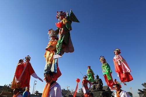 当日,民间艺人在呼和浩特大召广场表演脑阁