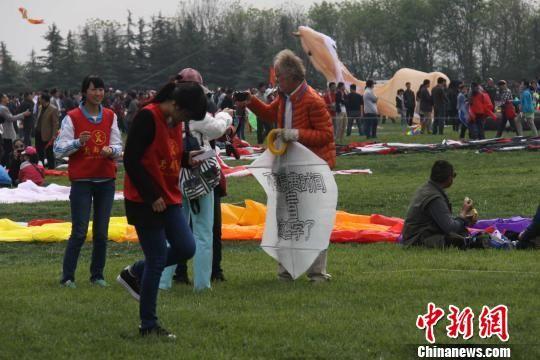 4月19日,第31届潍坊国际风筝会启幕。诺贝尔文学奖获得者莫言也于当日向家乡潍坊赠送题字风筝表祝福。图为国际友人和他的非主流风筝。 杨晓卫 摄