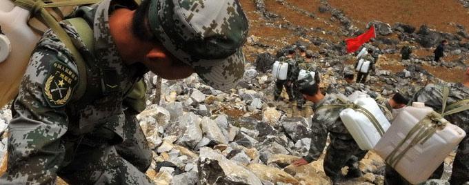 战士们在山间艰难行进为灾区送水