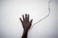 海地妇女手扶断壁残垣等待食物