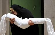 伊拉克妇女亲吻被白布包裹起来侄女
