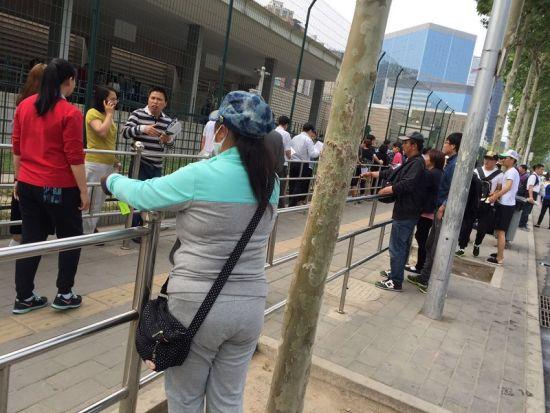 围栏内的长队和外面的存包生意人