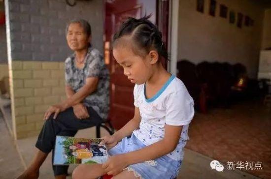 刘娜手里拿着妈妈和自己的合影仔细端详(7月28日摄)。