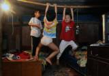 图文:三个孩子把晾衣竹竿当成高低杠