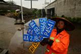 图文:暴雨后清洁工从积水中打捞出数块车牌
