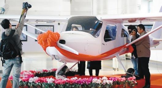 9月29日,来宾在L162飞机交付仪式上留影。当日,由中航工业沈阳飞机工业(集团)有限公司和美国赛斯纳飞机公司合作生产的我国第一架L162轻型运动飞机在沈阳正式交付客户。L162飞机主要适用于飞行训练、私人飞行和体育运动等领域。该飞机机身长约6.95米,机身重量约600公斤,搭载定员2人。 (新华社记者 姚剑锋 摄)