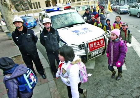 2日,在青岛德县路小学门前,一辆110警车停在门前,两名民警护送学生