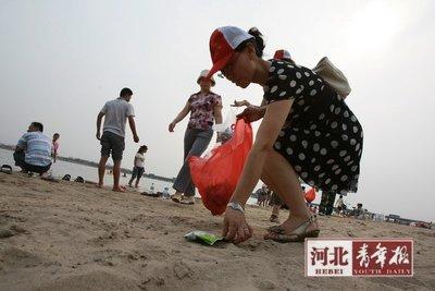 河北青年报讯(记者付聪)从秦皇岛专门拉来海沙打造成的石市新景观滹沱河黄金海岸7月1日通水后,游客纷至沓来。可是走在沙滩上零星的杂质随处可见,那不是美丽的贝壳,而是游人们丢弃的垃圾。这一现象被媒体曝光(本报也曾对此进行报道)后,引起不少市民关注。 东苑街道槐北二社区主任成云芝最先倡议大家捡垃圾。
