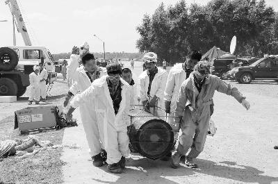 7月29日,人们在吉林省榆树市五棵树镇搬运化工物料桶.新华社照片