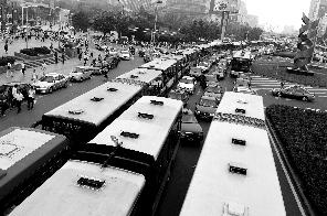 """2010年7月21日下午,中关村海淀黄庄路口北,进站的公交车排起长队,好像一列""""公交列车""""。本报资料图片 李飞 摄"""