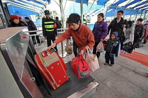 旅客在福州火车站进站口进行行李安检。