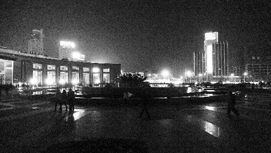 """26日晚8点半,济南泉城广场和主要繁华商业街等外围景观照明灯熄灭,迎接""""地球一小时""""。  本报记者 徐延春 摄"""