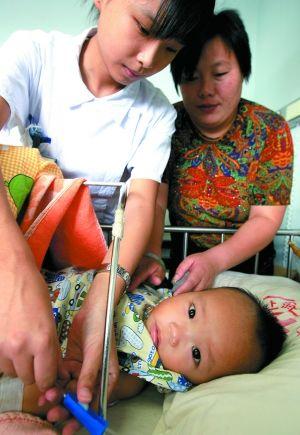 2008年9月13日,医务人员为10个半月大的肾衰竭患儿换药,该患儿因喝三鹿奶粉而患病。新华社记者 陈飞 摄