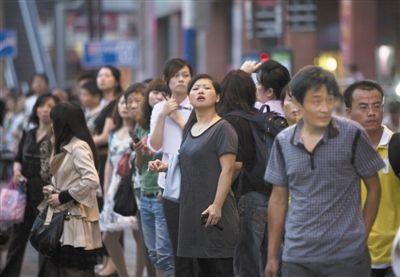 昨日,从上海海伦路站到老西门站应急公交疏散点等车的乘客们。 周岗峰 摄
