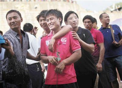 昨日,关累码头,一位船员手拿玫瑰花和朋友等候在岸边,迎接从泰国归来的船员老乡。本报记者 赵亢 摄