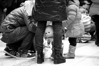 """带个娃娃回家,就得多照顾""""一口人"""",路上也多了几许乐趣。 本报实习记者 王德阳摄"""