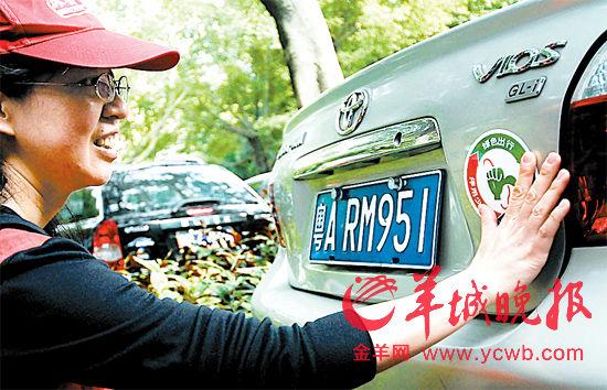 """深圳义工为响应""""绿色出行""""的车辆贴上标志。羊城晚报记者王磊摄"""