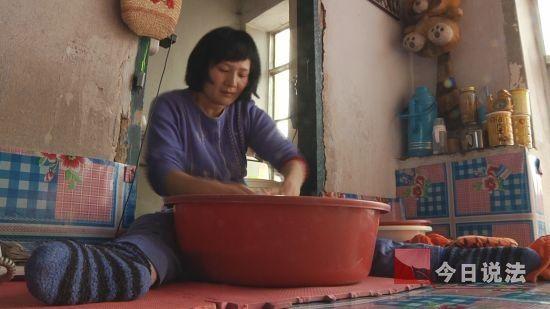 42岁的杨兆芳在家中洗衣服。几年前一场车祸毁掉了家庭,她高位截瘫。平日里大多数家务事都是杨兆芳自己做。