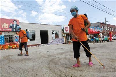 昨日,房山阎村镇张庄村,村民组成的防疫人员正对街道消毒。新京报记者 孙纯霞 摄