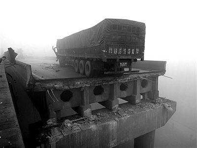 """2月1日,一辆""""豫G""""牌照的大货车停在桥面坍塌断裂处。这辆货车身后约80米长桥面发生坍塌事故,桥上的车辆也坠落到地面上。新华社发"""