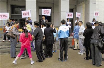 """2012年5月12日,一中学门口,报名""""小升初""""的家长和孩子在排队,准备测试特长。新京报资料图片"""