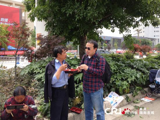 4月25日中午,灾民乐文清(中)在芦山县人民医院门前领到了一份免费餐,他边吃边向国际在线记者介绍家中受灾的情况。