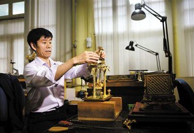 昨日,故宫博物院文保科技部,钟表修复专家正在修复被游客损坏的清代铜镀金转花水法人打钟。新京报记者 尹亚飞 摄