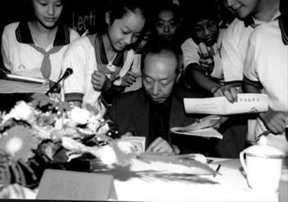 """2001年,在上海举行的""""空间周""""活动上,孙敬良为""""小航天迷""""们签名。"""