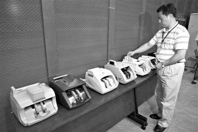 昨日,央行工作人员用各种验钞机对C1F9假币进行测试,机器均能及时作出异常报警?#20174;Α?#26032;京报记者 浦峰 摄