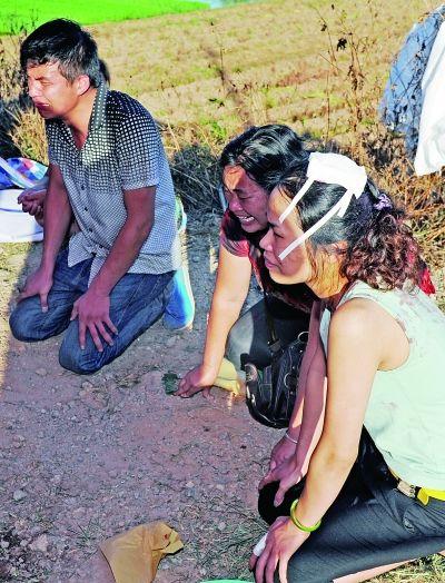 死亡瓜农邓正加的家人跪在他的尸体前,痛哭不已,他女儿(右)的头部,在昨日的冲突中受伤