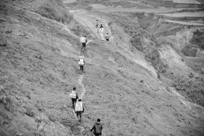 永光村受灾群众背着领到的救灾物资走过滑坡路面。