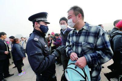 今天上午,在天安门广场,受到雾霾影响,警察戴着口罩执勤      摄/法制晚报记者 杨益