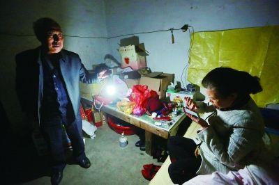 李素兰想从手机里找一个电话,赵作海拎过来家里唯一用于照明的13瓦的节能灯 摄/法制晚报记者 蒲晓旭