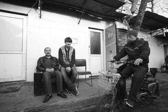 17日,达伍提(左)和他的兄弟坐在他开的餐馆前。
