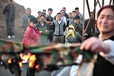 3月22日,杜家疃村村民在展示未被烧毁的帐篷外层覆盖物,村民称卖家宣称这种布料为防火布料,推测有人故意泼汽油纵火。现场有人用打火机点燃布料,布料稍微燃烧一会儿后自行熄灭。新京报记者 王嘉宁 摄