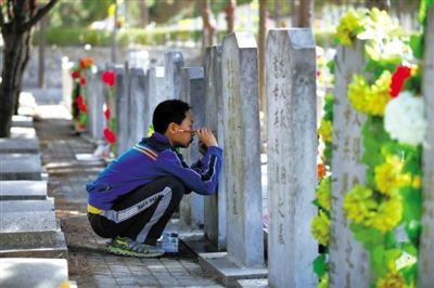 昨日,八宝山人民公墓,一位祭扫的男孩用毛笔为墓碑上的字描新。当日为今年清明第一个祭扫高峰日,5万人到八宝山扫墓。