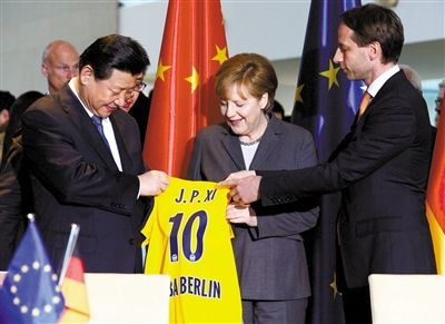 28日,柏林,欧绿保集团首席执行官Axel Schweitzer(右)向习近平赠送阿尔巴柏林篮球队球衣。