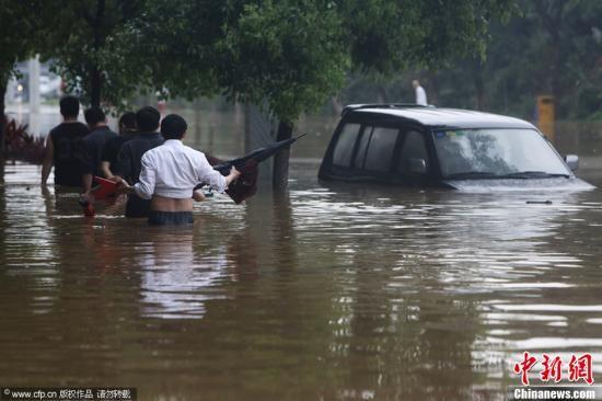 """3月31日,东莞南城绿色路因暴雨导致严重内涝,几辆机动车在积水深处""""抛锚""""了,包括一辆宝马X5。积水已经淹至宝马车窗以上部位。图为几名男子趟过齐腰深的积水接近一辆被淹的小车。苏仕日 摄 图片来源:CFP视觉中国"""