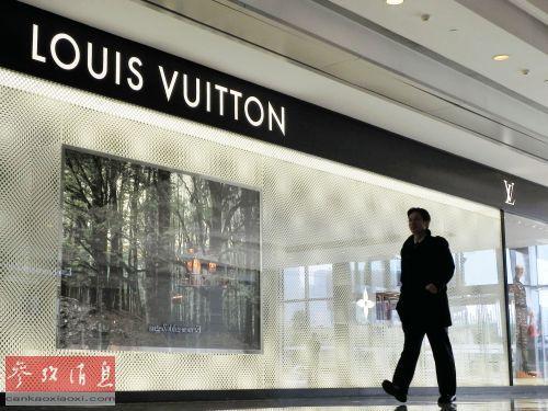 资料图片:2012年2月2日,行人从杭州一家路易威登专卖店的橱窗前走过。新华社发(龙巍 摄)