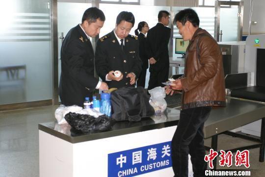 图为满洲里海关关员正在满洲里国际航空港对某出境中籍旅客的行李物品进行人工查验。 鲁焕新 摄