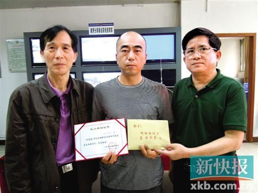 广州市见义勇为基金会两名负责人向单连波(中)颁发证书和慰问金。通讯员供图