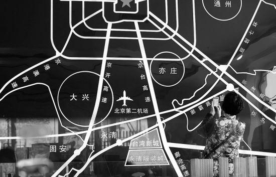在永清浙商新城,一名投资客正在拍摄国际服装城位置示意图。据永清台湾工业新城工委书记、管委会主任杨华彬介绍,京台高速在明年底开通后,仅半个小时就能到北京。尤其是北京新机场运营后,永清国际服装城优势更为明显。 摄/记者洪煜