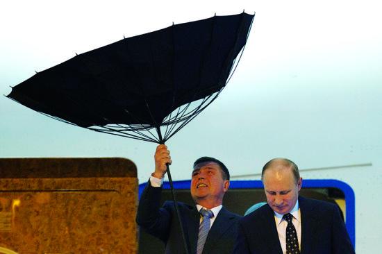 ▲刚出机舱,身边的安保人员急忙为普京打伞,因为风太大,雨伞一下子被吹翻