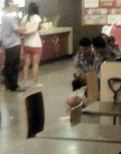一女嫌疑人(左二)和光头男子被控制。5月28日,在招远市一快餐店内,6人与一女受害者发生口角后将对方打死。视频截图