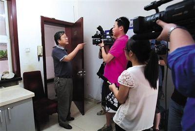 """昨日,北京市环境监察总队突查国家文物局食堂,文物局一工作人员想避开媒体与执法人员""""私聊""""被围住拍照,他激动地要求记者""""滚出去""""。本版图片/新京报记者 高玮"""